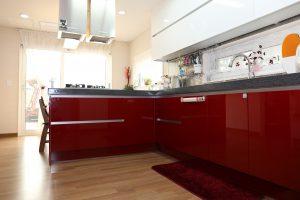 Keittiöremontilla saa kodin ilmeen uudistettua täysin. Kuvassa virtaviivainen ja pelkistetty keittö, jossa alakaapit punaiset ja yläkaapit valkoiset.