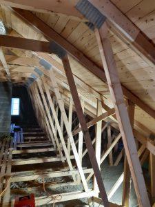 Kylmä ullakkotila ennen remonttia. Tilassa ei lattiaa ja kattorakenteet näkyvillä.